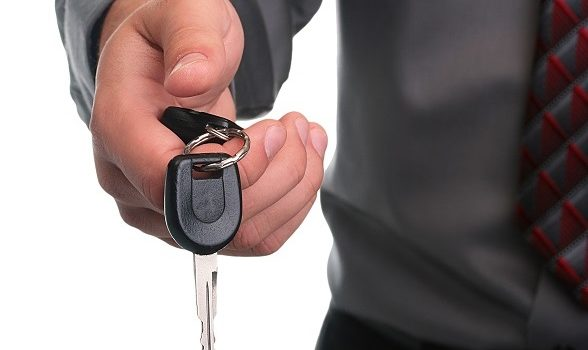 The businessman in a grey shirt and a tie stretches a car key.